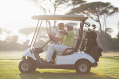 Mature golfer man pointing while sitting by friend Royalty Free Stock Photo