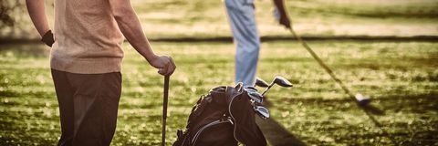 Mature golfer men standing on field. During sunny day stock image
