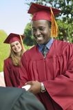 Mature Graduate Collecting Certificate From Dean Stock Photo