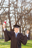 Mature graduate gesturing happiness in park Royalty Free Stock Photo