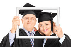 Mature graduates posing behind a picture frame Stock Photo