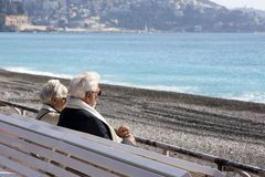 A mature, gray-haired beautiful couple: a man and a woman are sitting on a white bench on the Promenade des Anglais and looking at stock photos