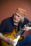 Mature guitarist with guitar and bandana Royalty Free Stock Images