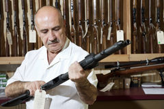 Mature gun shop merchant looking at rifle in store Stock Images