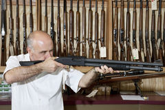 Mature gun shop merchant with rifle aiming Royalty Free Stock Photo
