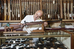 Mature gun shop owner looking at rifle in store Royalty Free Stock Photography
