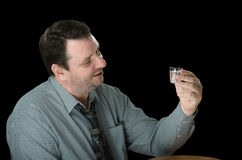 Mature guy looks at shot of vodka Royalty Free Stock Photo
