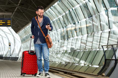 Mature guy on railway platform with bag and mobile phone. Full length portrait of mature guy walking with suitcase and looking at mobile phone on railway Royalty Free Stock Photography