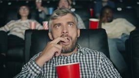 Mature guy watching scary film eating popcorn in dark modern cinema. Mature guy emotional spectator is watching scary film eating popcorn in dark modern cinema stock video footage