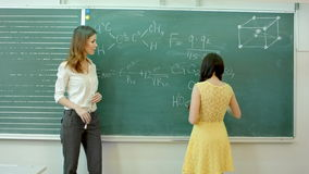 A mature hand writing or drawing on a green blackboard with a white chalk. stock footage