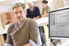 Mature handsome architect working on construction plan Stock Photos