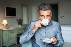 Mature businessman drinking coffee in a hotel room. Mature, handsome businessman drinking coffee in a hotel room royalty free stock image