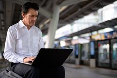 Mature handsome businessman using laptop computer in train station stock photos