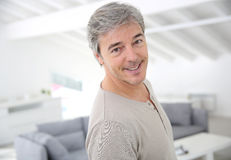 Mature handsome man smiling at home. Mature handsome man standing in modern house Royalty Free Stock Images