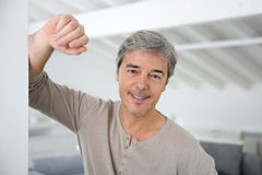 Mature handsome man standing at home. Mature handsome man standing in modern house Royalty Free Stock Photo