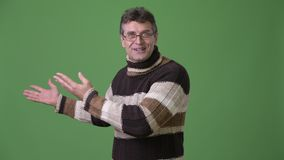 Mature handsome man wearing turtleneck sweater against green background