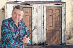 Mature handyman with hammer getting ready to tear Royalty Free Stock Photography