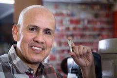 Mature handyman posing with duplicates of door keys Royalty Free Stock Image