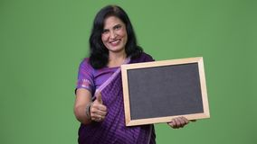 Mature happy beautiful Indian woman smiling while showing blackboard and giving thumbs up. Studio shot of mature beautiful Indian woman wearing traditional stock footage