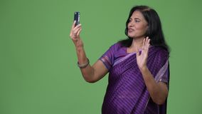 Mature happy beautiful Indian woman video calling using phone. Studio shot of mature beautiful Indian woman wearing traditional clothes against chroma key with stock video footage