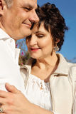 Mature happy couple. On a date outdoors wearing white against blue sky Stock Image