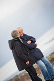 Mature happy couple walking on beach in autumn Stock Photos