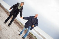 Mature happy couple walking on beach in autumn Stock Photo