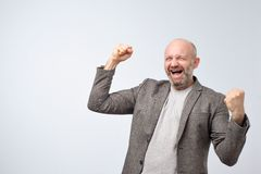 Mature happy laughing man in suit with raised hands over gray background. He is celebrating his winning or getting profits from financial project stock photos