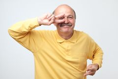 Mature happy man moving dancing over white background. Mature happy man in yellow t-shirt moving dancing over white background. He is enjoying every moment of royalty free stock photography