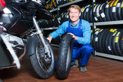 Mature happy mechanic holding new tyre for motorcycle. In workshop Stock Photo