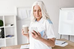 Mature happy woman drinking coffee using mobile phone. royalty free stock image