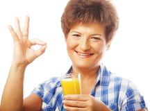 Mature happy woman with orange juice Royalty Free Stock Image