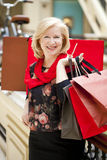 Mature happy woman with shopping bags. Mature happy blonde woman with shopping bags Royalty Free Stock Images