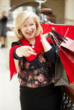 Mature happy woman with shopping bags Stock Photography
