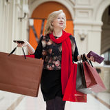 Mature happy woman with shopping bags Royalty Free Stock Image