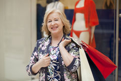 Mature happy woman with shopping bags. Mature happy blonde woman with shopping bags Royalty Free Stock Photo