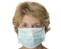 Mature healthworker with mask. Studio shot against a white background of older woman wearing a hospital mask royalty free stock images