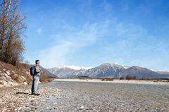 Mature hiker on the bank of a river. Walking toward mountain. Mature hiker on the bank of a river. Trekking toward  mountain. Rambler about 60 years old. Active Stock Photo