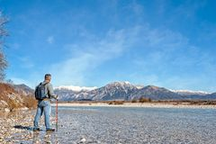 Mature hiker on the bank of a river. Walking toward mountain. Mature hiker on the bank of a river. Trekking toward  mountain. Rambler about 60 years old. Active Stock Image