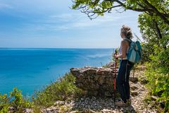 Mature hiker looking the sea. Travel and active lifestyle concept. royalty free stock images
