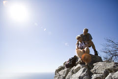 Mature hikers resting on clifftop edge overlooking Atlantic Ocean in bright sunlight, smiling, portrait Stock Photo