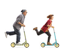 Mature Hipster And A Boy Riding Scooters Stock Images