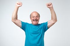 Mature hispanic man in blue t-shirt celebrating victory of his team over gray background. Football fan concept royalty free stock photo