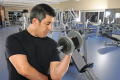 Mature Hispanic Man Exercising in Gym Stock Photo