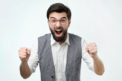 Mature hispanic man is happy with his win. He is holding his fists and shout Wow. stock image