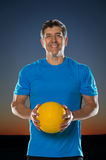 Mature Hispanic Man Holding Volleyball Stock Image