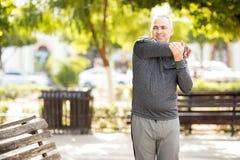 Mature hispanic man stretching arms before workout stock photo