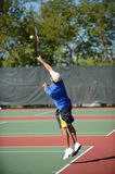 Mature Hispanic tennis player. Serving during a match Stock Photography