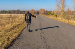 Mature hitchhiker walking on a road Royalty Free Stock Images