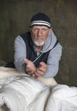 Mature homeless man looking fed up, holding out his hands Stock Images